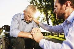 Der alte Mann ist auf einem Rollstuhl und dem Mann im Park Der alte Mann ist, der Mann versucht, ihn zu stützen traurig Lizenzfreies Stockfoto