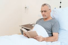 Der alte Mann liegt auf einem Feldbett im medizinischen Bezirk und liest ein Buch Er setzte an seine Gläser Lizenzfreies Stockbild
