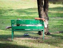 Der alte Mann mit Armbanduhr und dem Tragen eines weißen Cowboyhuts stand auf einem grünen Stuhl im Garten still Lizenzfreie Stockfotografie