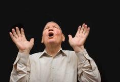 Der alte Mann mit Gefühlen auf einem dunklen Hintergrund Stockfotografie
