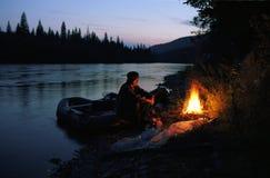 Der alte Mann sitzt auf der Flussbank durch das Feuer Stockfotografie