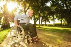 Der alte Mann sitzt auf einem Rollstuhl im Park und versucht zu gehen Stockbild