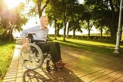 Der alte Mann sitzt auf einem Rollstuhl im Park und versucht zu gehen Lizenzfreie Stockfotos