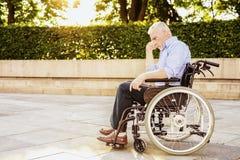Der alte Mann sitzt in einem Rollstuhl im Park Lizenzfreies Stockfoto
