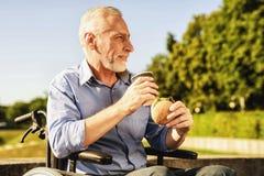 Der alte Mann sitzt in einem Rollstuhl und in einem Essen Er lächelt Stockfotografie