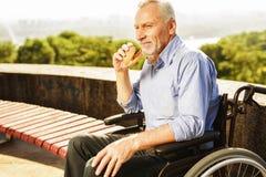 Der alte Mann sitzt in einem Rollstuhl und in einem Essen Er lächelt Stockbild