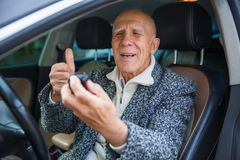 Der alte Mann sitzt im Auto, untersucht die Aktionskamera und zeigt Daumen-oben Lizenzfreies Stockbild