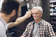 Der alte Mann sitzt im Friseur ` s Stuhl in einem Mann ` s Friseursalon, wohin er kam, sein Haar zu schneiden Lizenzfreies Stockfoto
