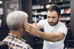 Der alte Mann sitzt im Friseur ` s Stuhl in einem Mann ` s Friseursalon, wohin er kam, sein Haar zu schneiden Lizenzfreie Stockfotos