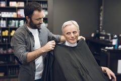 Der alte Mann sitzt im Friseur ` s Stuhl in einem Mann ` s Friseursalon, wohin er kam, sein Haar zu schneiden Lizenzfreies Stockbild