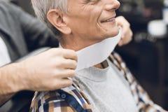 Der alte Mann sitzt im Friseur ` s Stuhl in einem Mann ` s Friseursalon, wohin er kam, sein Haar zu schneiden Stockbilder