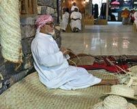 Der alte Mann spinnt Strohhüte, um Gäste im pavilio zu treffen Stockfotografie