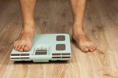 Der alte Mann steht auf einer modernen Skala Messen des Fettgehaltes des Körpers Intelligentes medizinisches Gewicht Das Konzept  Lizenzfreies Stockfoto