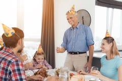 Der alte Mann steht nahe der festlichen Tabelle und hält ein Glas Saft in seinen Händen Er spricht einen Toast Lizenzfreie Stockfotografie