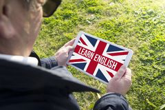 Der alte Mann, der Tablette mit hält, lernen englische APP Stockfoto
