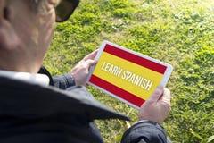 Der alte Mann, der Tablette mit hält, lernen spanische APP Stockfotografie