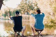 Der alte Mann und sein erwachsener Sohn sitzen auf der Bank des Flusses in den Klappstühlen und in anziehenden Fischen auf den sp Stockbilder