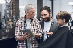 Der alte Mann zeigt dem Friseur etwas auf der Tablette Stockfoto