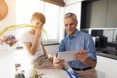 Der alte Mann zeigt seinem Enkel etwas, sitzt sein Enkel nahe bei ihm und täuscht herum Stockfoto