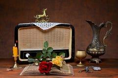 Der alte Radio, ein Metallkrug und Rosen Lizenzfreie Stockfotos