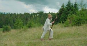 Der alte Reisende in der alten Kleidung geht mithilfe des Stocks und hält die Feldblumen Der Gebirgsstandort stock video footage
