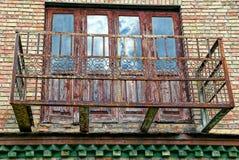 Der alte rostige Metallrahmen des Balkons auf der Wand des Hauses Stockfoto