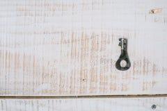 Der alte Schlüssel auf einem weißen hölzernen Hintergrund Beschneidungspfad eingeschlossen Stockfotos