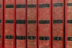 Der alte Stapel von roten Büchern im Regal Stockbild