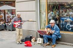Der alte Straßenmusiker, der Gitarre auf den alten Straßen von Lemberg spielt Lizenzfreie Stockbilder
