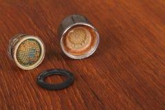 Der alte und benutzte Absperrhahn auf Holz Stockfotografie