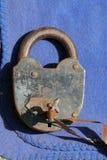 Der alte verrostete Metallverschluß mit einem Schlüssel auf einem blauen Farbstoff Lizenzfreies Stockbild