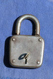 Der alte verrostete Metallverschluß mit einem Schlüssel auf einem blauen Farbstoff Lizenzfreie Stockfotos