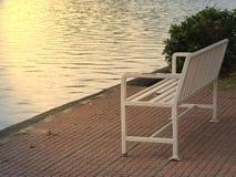 Der alte weiße Stuhl, der den Fluss bei Sonnenaufgang bereitsteht lizenzfreie stockbilder
