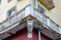 Der alte zerstörte Balkon an der Ecke des Hauses Rostig und mit den Elementen, die weg von Zeit geflogen sind Lizenzfreie Stockfotografie