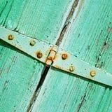 in der alten Wand ein Klappfenstergrünholz und ein rostiges Metall Lizenzfreie Stockfotos