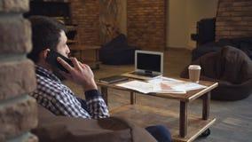 Der Analytiker, der am Telefon auf einer Tabelle spricht, breitete Arbeitspapiere aus stock video