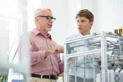 Der angenehme ältere Mann, der mit Interniertem sich verständigt, beim Druck von 3D modelliert lizenzfreie stockbilder