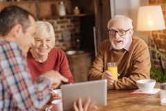 Der angenehme Mann, der seinen älteren Personen Video zeigt, erzieht am Frühstück stockfotos
