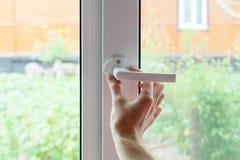 Der Angestellte öffnet eine Schutzkappe vom Element des Plastikfensters Vorbereiten eines Plastikfensters für Kleinreparaturen stockbild