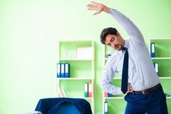 Der Angestellte, der Übungen während des Bruches bei der Arbeit tut stockfotos