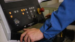 Der Angestellte steht am Bedienfeld der Maschine mit numerischer Steuerung Es steuert den Prozess einer Computermaus und -bU stock footage