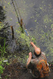 Der Angleramateur mit einer selbst gemachten Angelrute auf dem Ufer von t Stockfoto