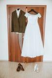 Der Anzug des Bräutigams und das Kleid der Braut, Heiratsausstattungen für Paare, hängend am Gestell Stockfotos