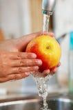 Der Apfel wird im Wasser gewaschen Stockfotos