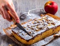 Der Apfelkuchen, abgewischt mit Puderzucker und der Hand schneidet den Kuchen Re Lizenzfreies Stockbild