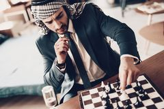 Der arabische Geschäftsmann, der Schach spielt und erwägt Bewegung lizenzfreies stockfoto