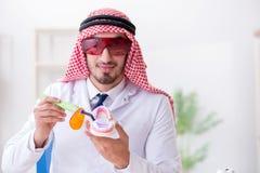 Der arabische Zahnarzt, der an neuem Zahnimplantat arbeitet stockfoto