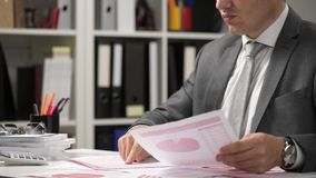 Der arbeitende und berechnende Geschäftsmann, liest und schreibt Berichte Büroangestellter, Tabellennahaufnahme Conce Finanzbuchh stock footage
