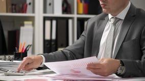 Der arbeitende und berechnende Geschäftsmann, liest und schreibt Berichte Büroangestellter, Tabellennahaufnahme Finanzbuchhaltung stock video footage