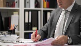 Der arbeitende und berechnende Geschäftsmann, liest und schreibt Berichte Büroangestellter, Tabellennahaufnahme Finanzbuchhaltung stock video